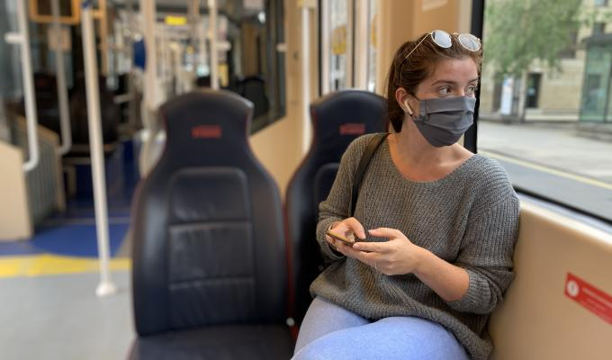 Girl wearing face mask on tram looking out of window