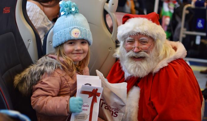 santa handing pack to kid on tram